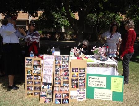 "Members of Phoenix International Folk Dancers ""woman"" their information table."
