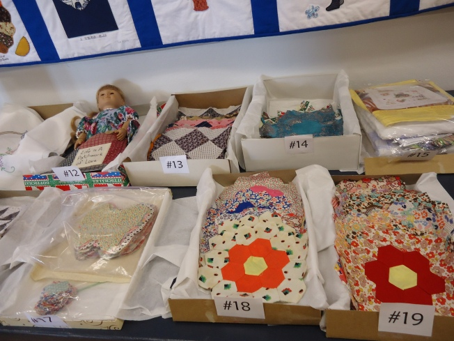 Silent auction items, including antique quilt blocks.