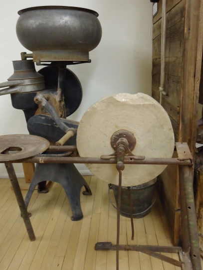 A grinding wheel, and behind it, a devise used to separate cream from milk.