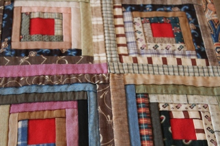 Closeup of hand-sewn log cabin quilt.