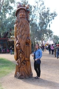 Katie next to a huge wooden carving